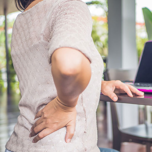woman holding her hip due to sciatica pain