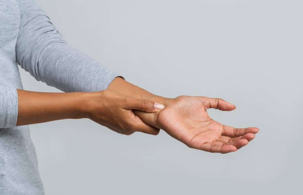 female holding her wrist due to carpal tunnel pain