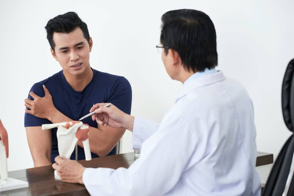 young patient speaking to his doctor about his shoulder pains