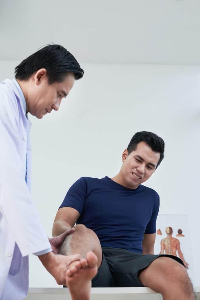 chiropractor examining male patients knee
