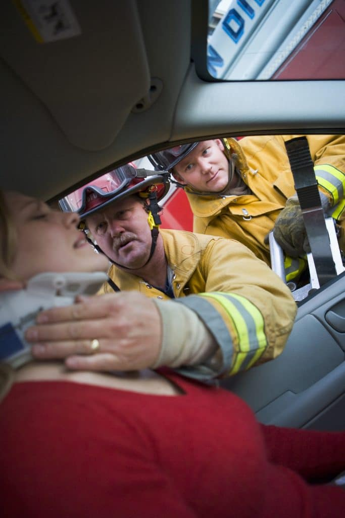 firefighters helping a female out of her car from a recent car accident