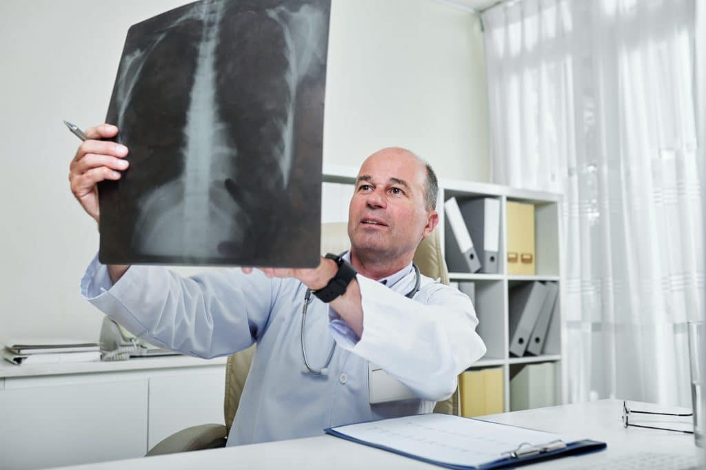 chiropractor looking at patient upper and lower back x-ray