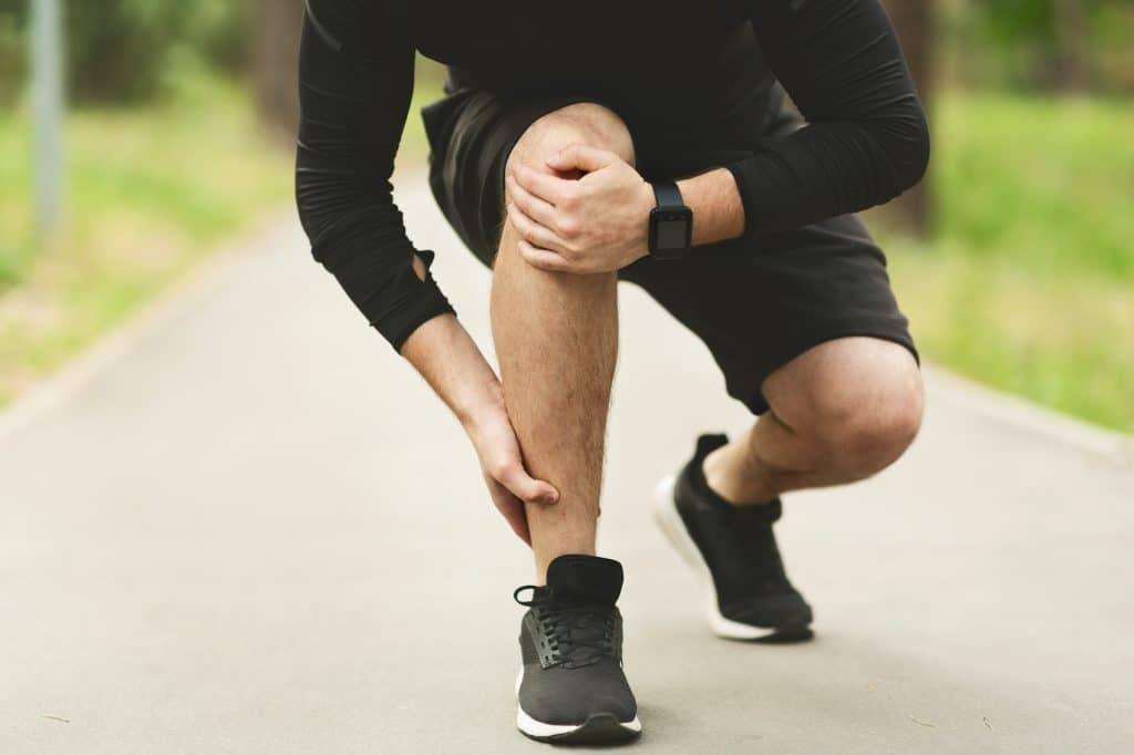 male runner holding his leg and knee due to pain