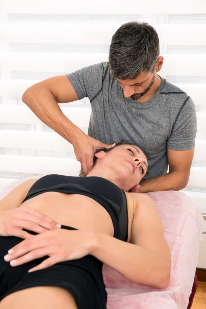 chiropraactor adjusting female patient neck