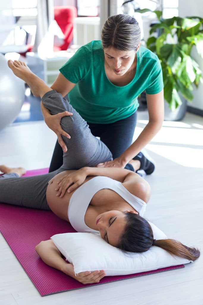 chiropractor adjsuting pregnant patients lower back and hips