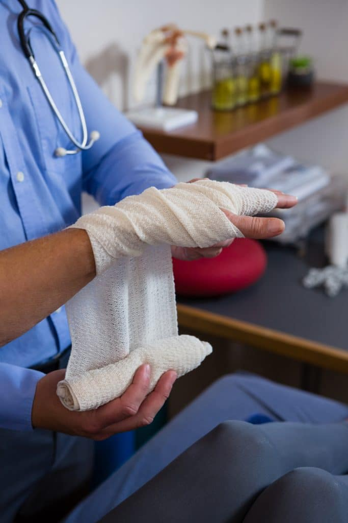 doctor wrapping patients hand with a bandage