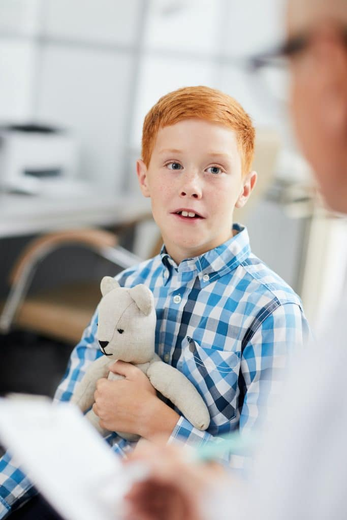 Red-Haired Boy Talking to a Doctor
