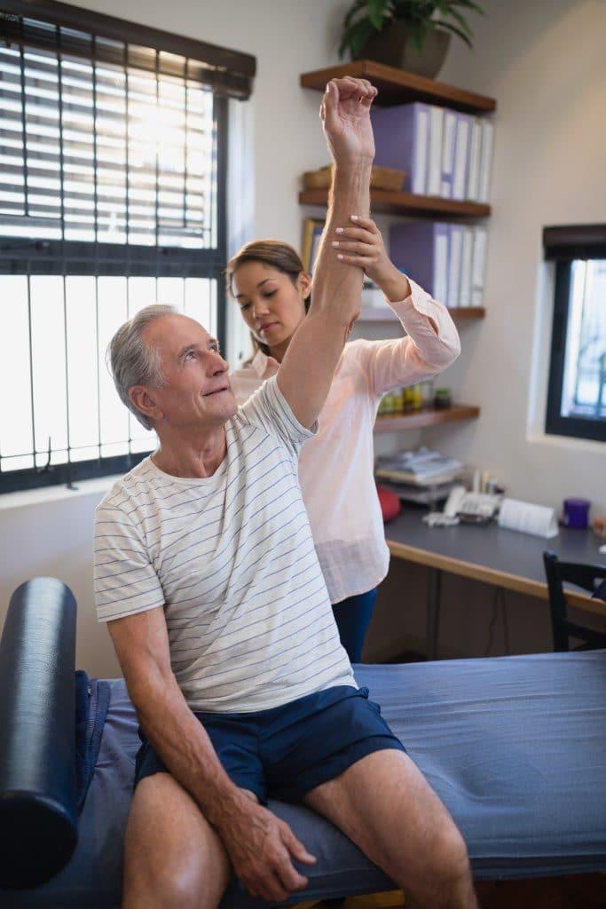 chiropractor examining elderly patients shoulder
