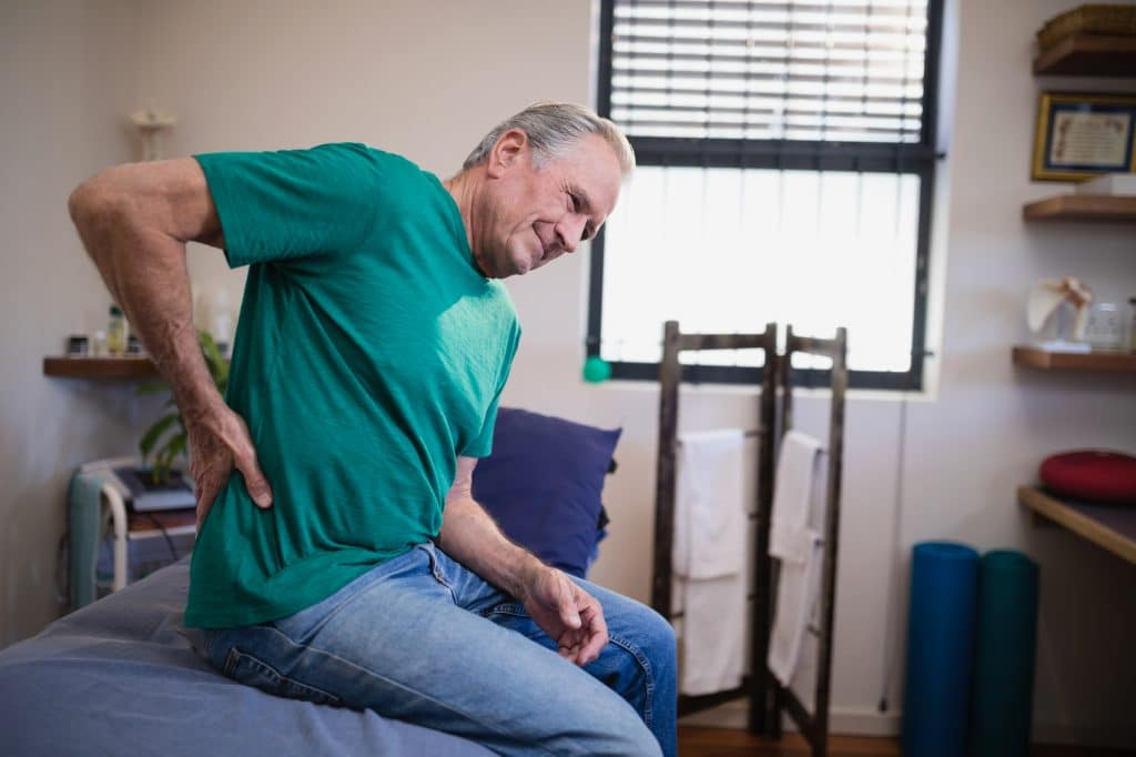 elderly man holding his hip due to pain