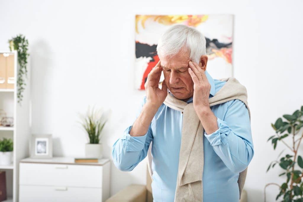 elderly man having headaches