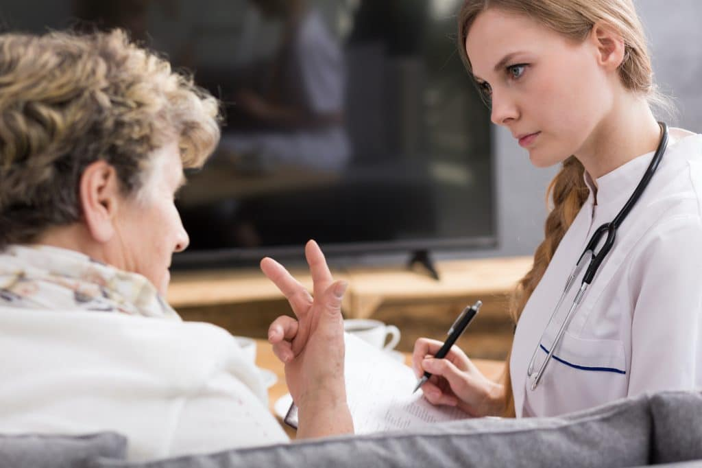 elderly woman speaking to her doctor about health concerns